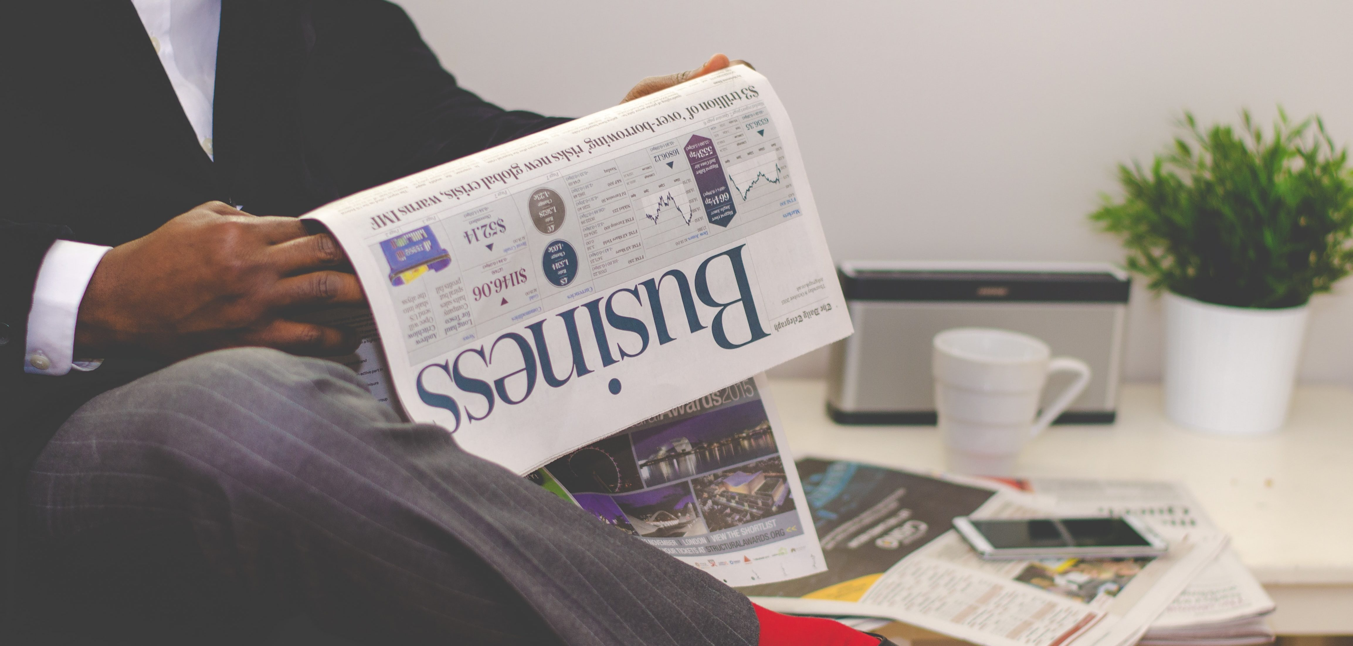 A man in a suit sits reading the business section of a newspaper